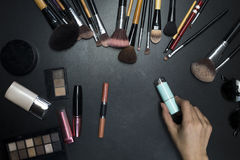 A hand holding cosmetics on black background. Copy space Stock Images