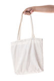 Hand holding cotton eco bag on white background Stock Photography