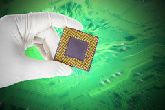 Hand holding a CPU. On circuit board background Stock Photos