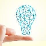 Idea and innovation concept. Hand holding creative light bulb sketch on subtle light background. Idea and innovation concept stock photography
