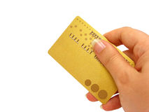 Hand holding credit card (clipping path included). Female hand holding a golden credit card with clipping path Royalty Free Stock Photography