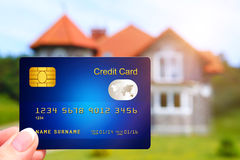 Hand holding credit card with house as a background Stock Photo
