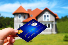 Hand holding credit card with house as a background Royalty Free Stock Image