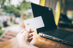 Hand holding credit card with laptop in background Royalty Free Stock Images