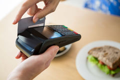 Hand holding a credit card next to the digital tablet in the coffee shop Royalty Free Stock Photography