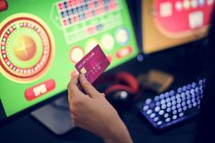 Hand holding credit card playing online gambling royalty free stock photography
