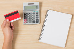 Hand holding credit card and put calculator, notebook on wood Royalty Free Stock Photo