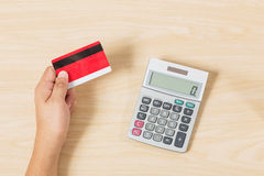 Hand holding credit card and put calculator on wood Stock Image