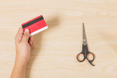 Hand holding credit card and put scissors on wood Stock Photography