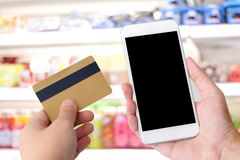 Hand holding credit card and smart phone with blank screen over stock photography