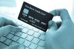 Hand holding a credit card and typing. Royalty Free Stock Image