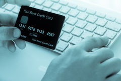 Hand holding a credit card and typing. Stock Photos