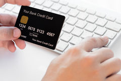 Hand holding a credit card and typing. Stock Photography