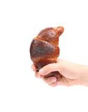 Hand holding croissant with poppy. Stock Photos