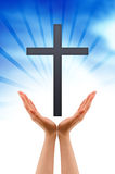 Hand holding a Cross. Hand holding a religious sign on cloud background Royalty Free Stock Photography