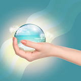 Hand holding crystal ball with beach and sea Royalty Free Stock Images