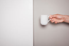 Hand holding a cup against dual colored background Royalty Free Stock Photo