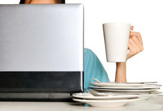 Hand holding cup behind laptop and stack of dirty plates on desk Stock Photography