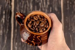 Hand holding cup of coffee beans on black rusty background with. soft focus. copy space stock photo