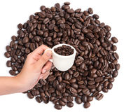 Hand holding cup of coffee beans on coffee beans background Royalty Free Stock Photo