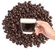 Hand holding cup of coffee on coffee beans background Stock Photos