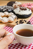 Hand Holding Cup of Coffee, Doughnut or Donut Stock Photography