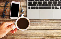 Hand holding cup of coffee with glasses,earphone and smart phone Stock Photography