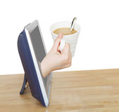 Hand holding cup of coffee with milk leans out TV Royalty Free Stock Photo