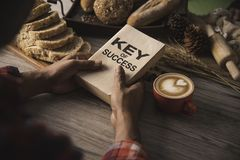 Hand holding a cup of coffee and reading a book key of success - royalty free stock photography