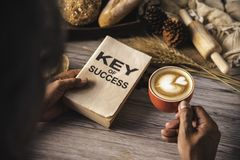 Hand holding a cup of coffee and reading a book key of success - stock photo