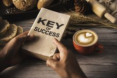 Hand holding a cup of coffee and reading a book key of success - stock photography
