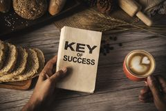 Hand holding a cup of coffee and reading a book key of success - royalty free stock image