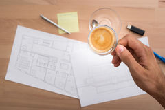 Hand holding a cup of coffee while working Royalty Free Stock Images