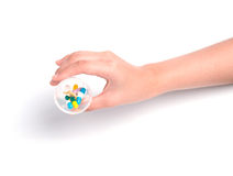 Hand holding cup of drug capsule on white background Stock Photography