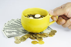 Hand Holding cup full with money Royalty Free Stock Photography