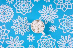 Hand holding cup of hot chocolate with marshmallow and paper snowflakes on blue background. Top view. Christmas decoration royalty free stock images