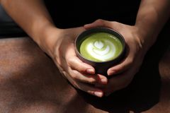 Hand holding cup of traditional Japanese hot matcha green tea latte art with strong light and copy space stock photo