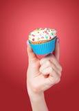 Hand holding cupcake Stock Image