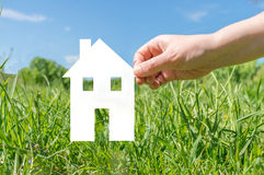 Hand holding cut off paper house as symbol of mortgage Stock Image