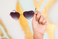 Hand holding cute sunglasses in front of colorful mural royalty free stock photography