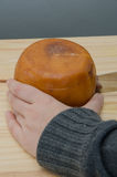 Hand holding and cutting a Cheese wheel Royalty Free Stock Photos