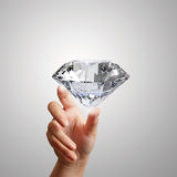 Hand holding 3d diamond over white Stock Photo