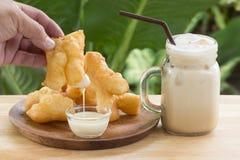 Hand holding deep fried dough stick Stock Photos