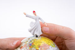 Hand holding a Derviş on a globe Royalty Free Stock Images