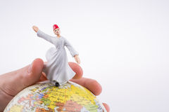 Hand holding a Derviş on a globe Royalty Free Stock Photos