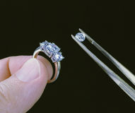 Hand holding diamond ring and stone with tweezers Royalty Free Stock Images