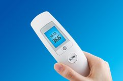 Hand holding digital contactless thermometer. On blue background Royalty Free Stock Photo