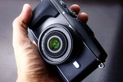 Hand holding a digital mirrorless camera Stock Photography