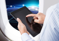 Hand holding digital tablet in airplane with horizon background. Businessman holding digital tablet in airplane with social and horizon background Stock Photos