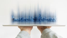 Hand holding digital tablet with futuristic modern buildings hologram on screen stock photo